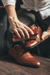 bootblack cleans brown monk shoes with a brush and shoe polish