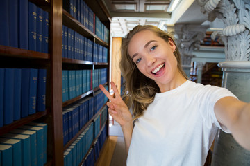 Excited young girl standing in traditional old library at bookshelves, smiling and laughing student making selfie on phone camera, having fun. Higher education and Student life concept.