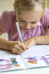 Smiling little girl writing numbers in exercise book