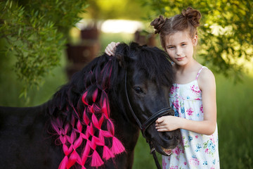 Cute little girl with black pony in the park