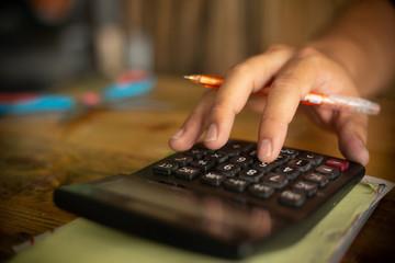 Close up man hand using calculator.