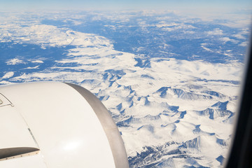 Winter mountain landscape with snow-capped peaks from the airplane window