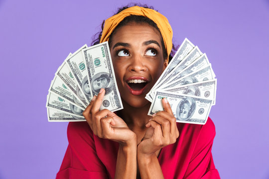 Image of Cheerful african woman in dress holding money