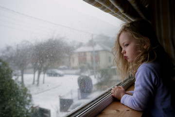 Little girl looking out the window at the snow