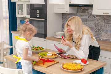 The mother tells her daughter how to cut vegetables correctly, the concept of cooking.