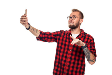 Lifestyle concept: a young man with a beard in shirt holding mobile phone and making photo of himself while standing against white background.