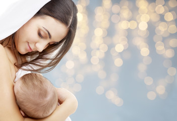 family, breastfeeding and motherhood concept - happy young mother with little baby sucking breast over festive lights background