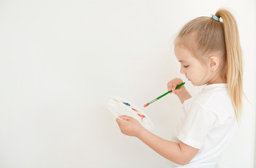 View from behind of a little girl painting on blank white wall.