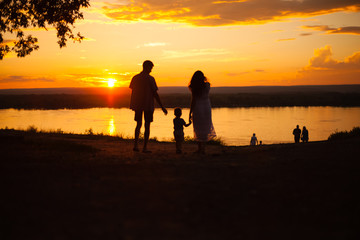family, silhouettes of mom and dad on a background of beautiful sky, sunset, family at sunset