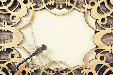 Openwork wooden frame with a dragonfly