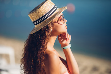 Close-up outdoor portrait of blissful ginger woman enjoying sea breeze. Photo of attractive female model with long dark hair in hat enjoying photoshoot on sea