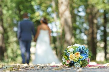 Brautpaar im park mit Brautstrauss