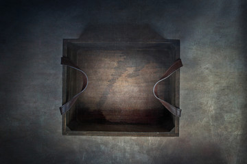 Old rustic wooden box with leather straps over a dark background. Image shot from above.