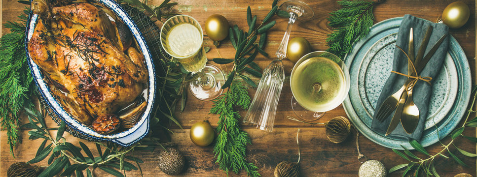 Christmas or New Year celebration table setting. Flat-lay of roast chicken or turkey, plates, silverware, glass and toy holiday decoration over rustic wooden background, top view, copy space
