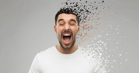 emotions, stress and people concept - crazy shouting man in t-shirt over gray background with particle dispersion effect