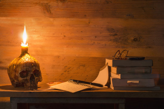 Skulls ,book,pen,glasses and candle on wooden table in candlelight at dark room to creative for design and decoration on background.Copy space.Concept halloween day.