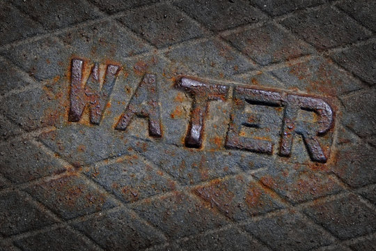 Water Sign on Metal Cover of Manhole