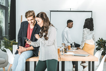 multicultural business people using smartphone while coworkers discussing work in office