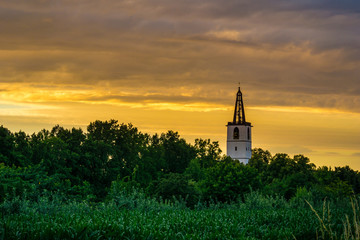 Germany, Church spire of denzlingen next to Freiburg orange twilight mood