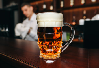 Glass of beer with foam is standing on the wooden bar counter. Old pub with bartender cleaning the dishes on background. Leisure, fun and friends concepts photo.