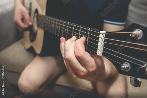 Man at home is playing the guitar. Guys hands are taking the chord ...