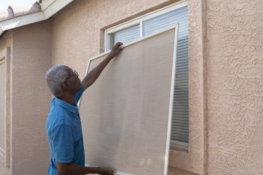 Senior man installing a window screen.