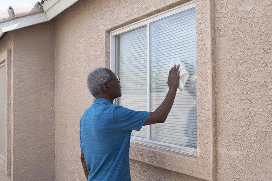 Senior washing a home window