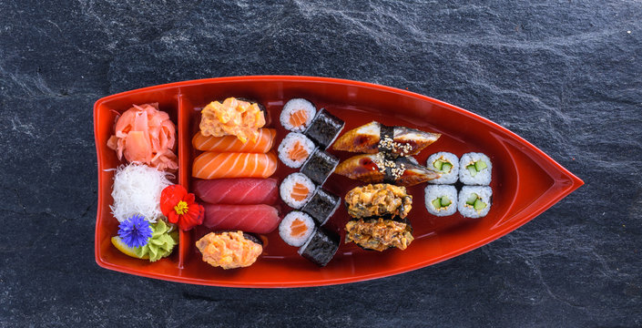 Set of sushi on stand in the form of the boat on stone back
