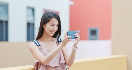Woman taking photo with cellphone in shenzhen city