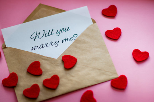 "The envelope with a note ""Will you marry me?"" and carved hearts on pink background. Marriage proposal concept."