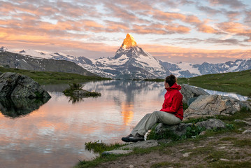 Morning shot of the golden Matterhorn (Monte Cervino, Mont Cervin) pyramid and  blue Stellisee lake. Female tourist enjoying view of early morning Matterhorn mountain is Valais Alps, Switzerland.