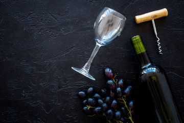 Composition with wine. Red wine bottle, bunch of grapes, corkscrew, wine glass on black background top view copy space