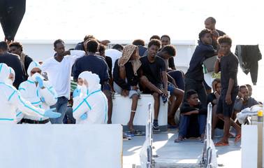 "Migrants wait to disembark from the Italian coast guard vessel ""Diciotti"" at the port of Catania"