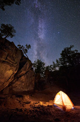 Mountain campsite at summer night amid huge steep rock formation. Small tourist tent brightly lit by burning campfire under clear dark starry sky. Tourism, climbing, hiking and traveling concept.