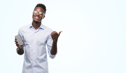 Young african american man using smartphone pointing with hand and finger up with happy face smiling