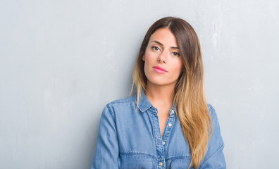 Young adult woman over grey grunge wall wearing denim outfit with a confident expression on smart face thinking serious