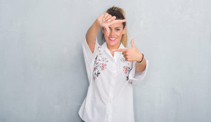 Young adult woman over grunge grey wall wearing flowers shirt smiling making frame with hands and fingers with happy face. Creativity and photography concept.