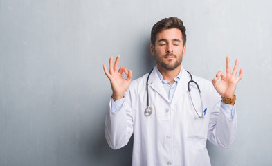 Handsome young doctor man over grey grunge wall relax and smiling with eyes closed doing meditation gesture with fingers. Yoga concept.