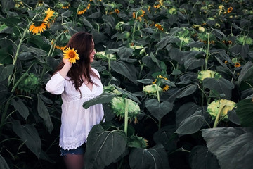 Young girl with sunflowers in the bright sun