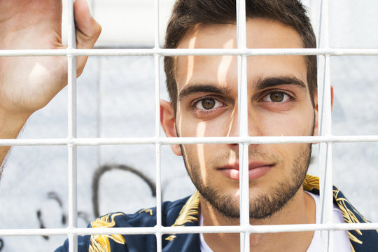 portrait of a young man behind bars or fences