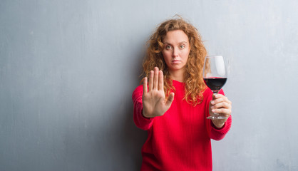 Young redhead woman over grey grunge wall drinking a glass of wine with open hand doing stop sign with serious and confident expression, defense gesture