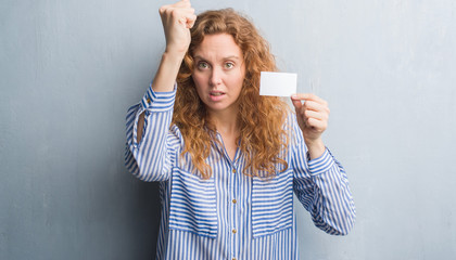 Young redhead woman over grey grunge wall holding blank visit card annoyed and frustrated shouting with anger, crazy and yelling with raised hand, anger concept
