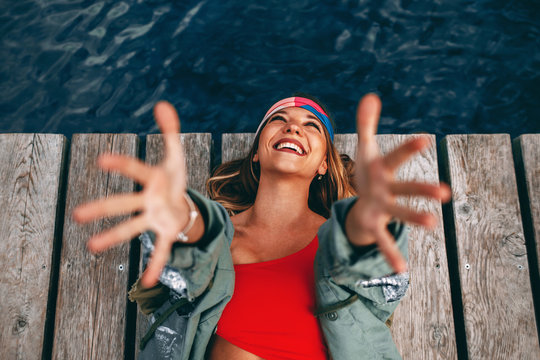 Young happy woman laying on the dock with arms raised