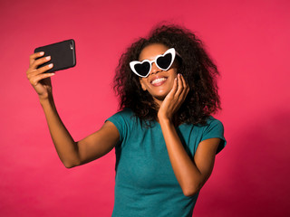 Smiling happy young african american girl in green t-shirt and heart shaped sunglasses making selfie photo on smartphone over pink background. Technology concept.