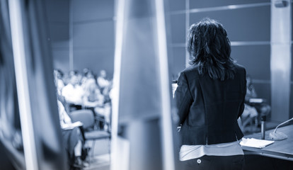 Female speaker giving a talk on corporate business conference. Unrecognizable people in audience at conference hall. Business and Entrepreneurship event. Black and white, blue toned image.