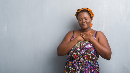 Young african american woman over grey grunge wall wearing orange braids smiling with hands on chest with closed eyes and grateful gesture on face. Health concept.