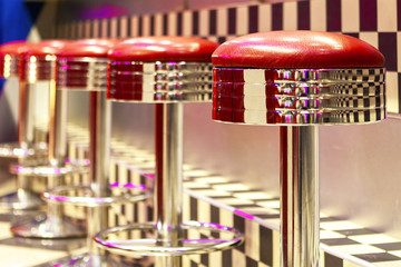 Vintage Row of metal bar stools, interior, red metal chairs near the bar.