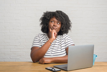 Young african american woman sitting on the table using computer laptop serious face thinking about question, very confused idea