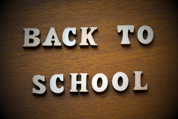 Vignetting. The inscription back to school laid out of wooden letters on a brown background.