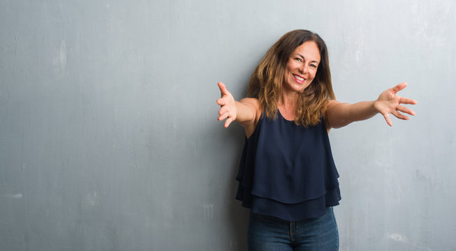 Middle age hispanic woman standing over grey grunge wall looking at the camera smiling with open arms for hug. Cheerful expression embracing happiness.